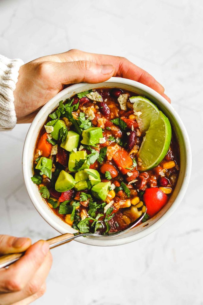 holding a bowl of Instant Pot Vegan Chili in a white bowl