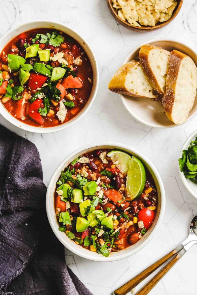 Instant Pot Vegan Chili in two white bowls with bread