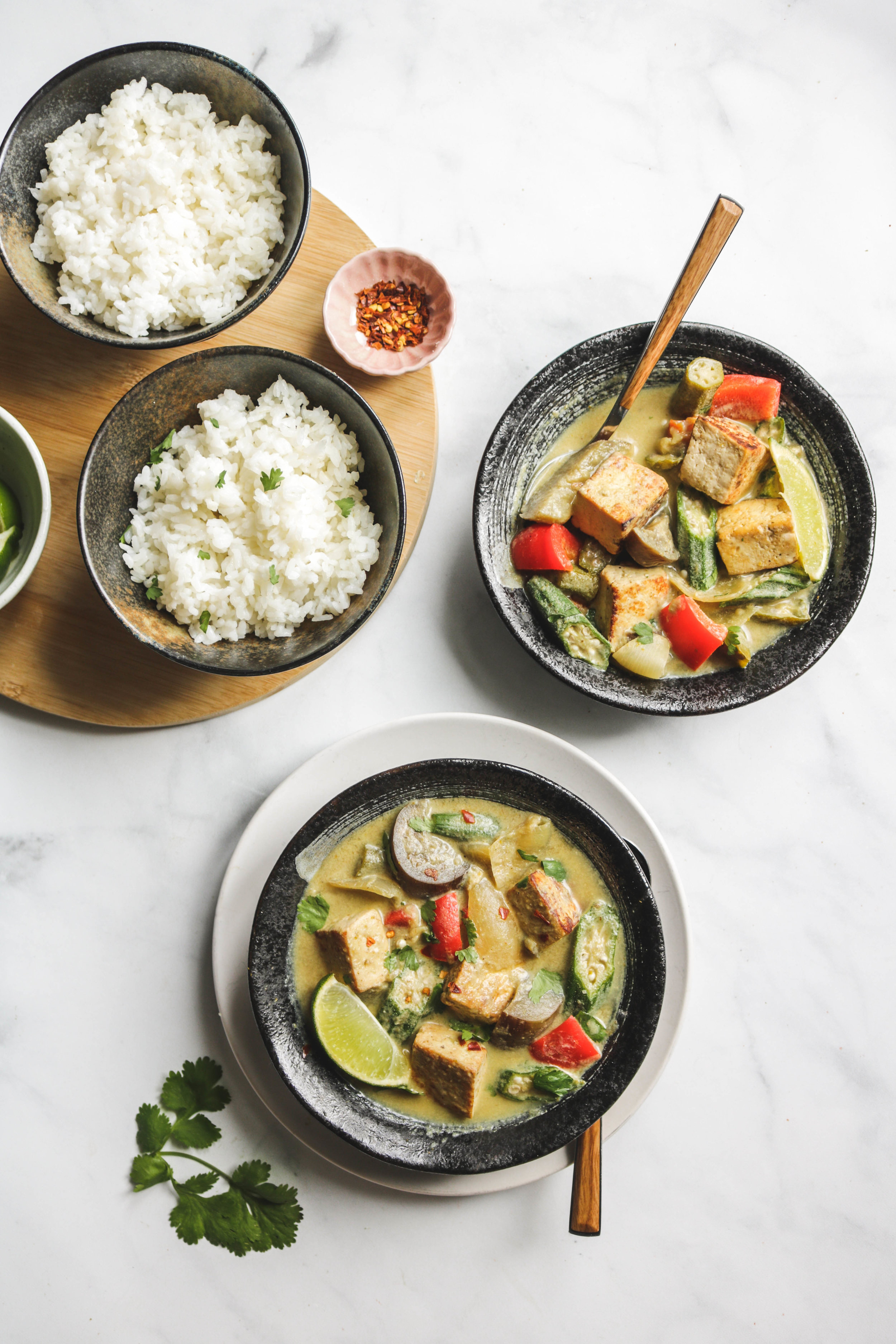 thai green curry with tofu, vegetables and rice in a black bowl