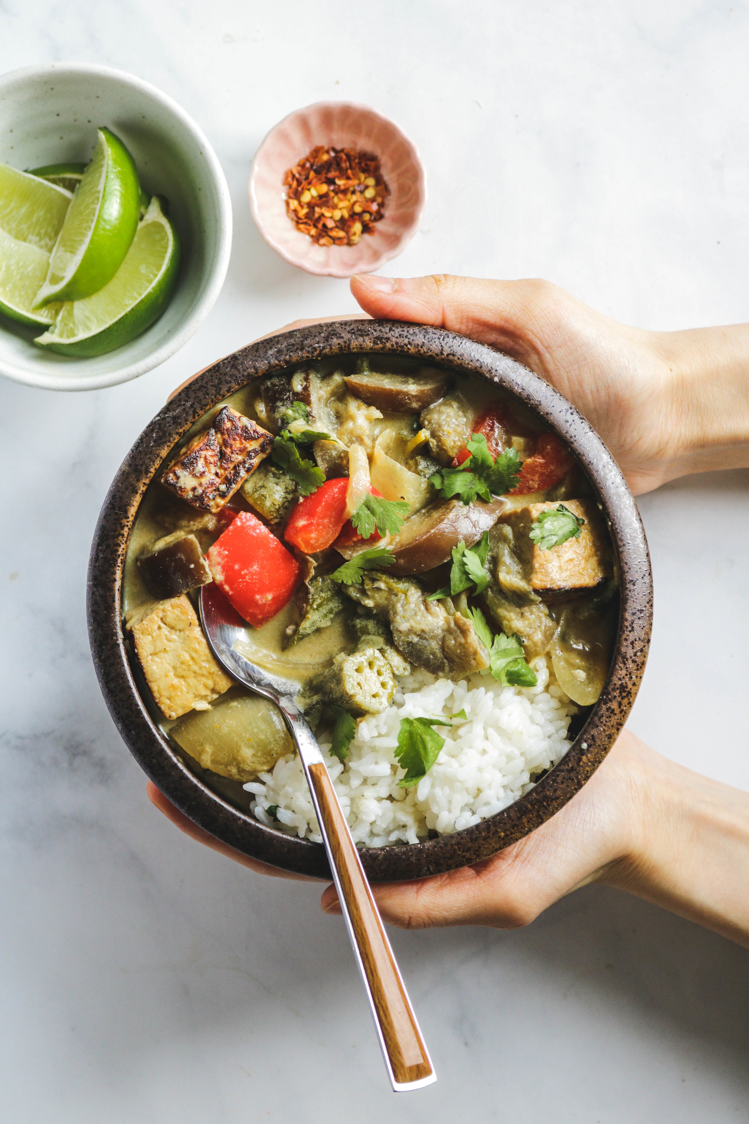 vegan thai green curry with tofu and summer vegetables in brown bowl