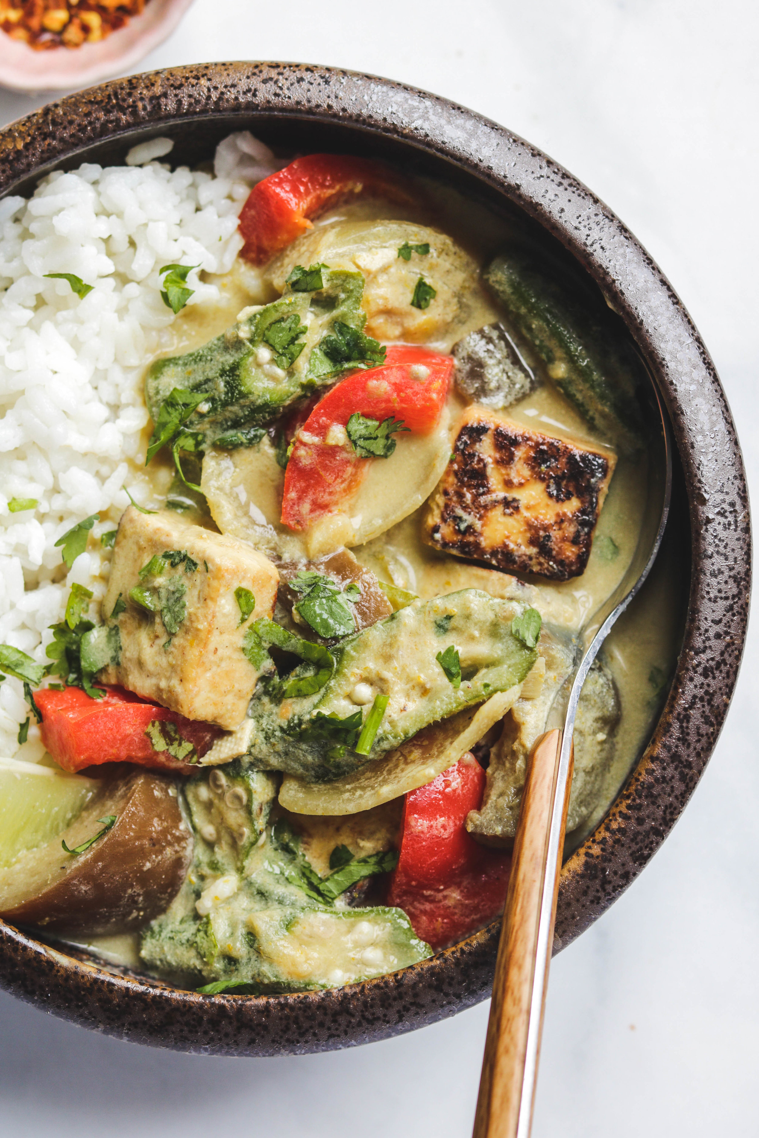 vegan thai green curry with tofu and summer vegetables close up