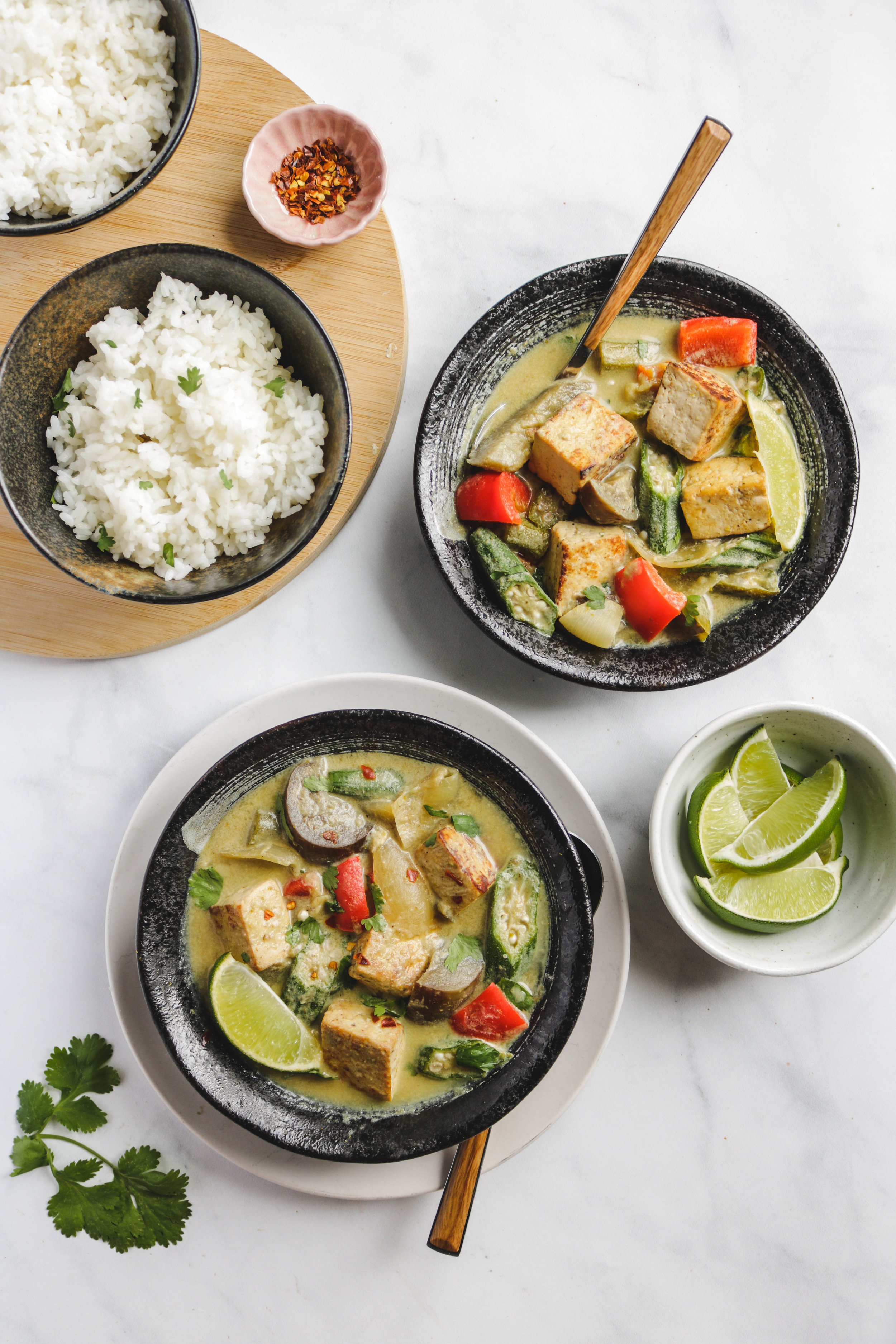 vegan thai green curry with tofu and summer vegetables in black bowl