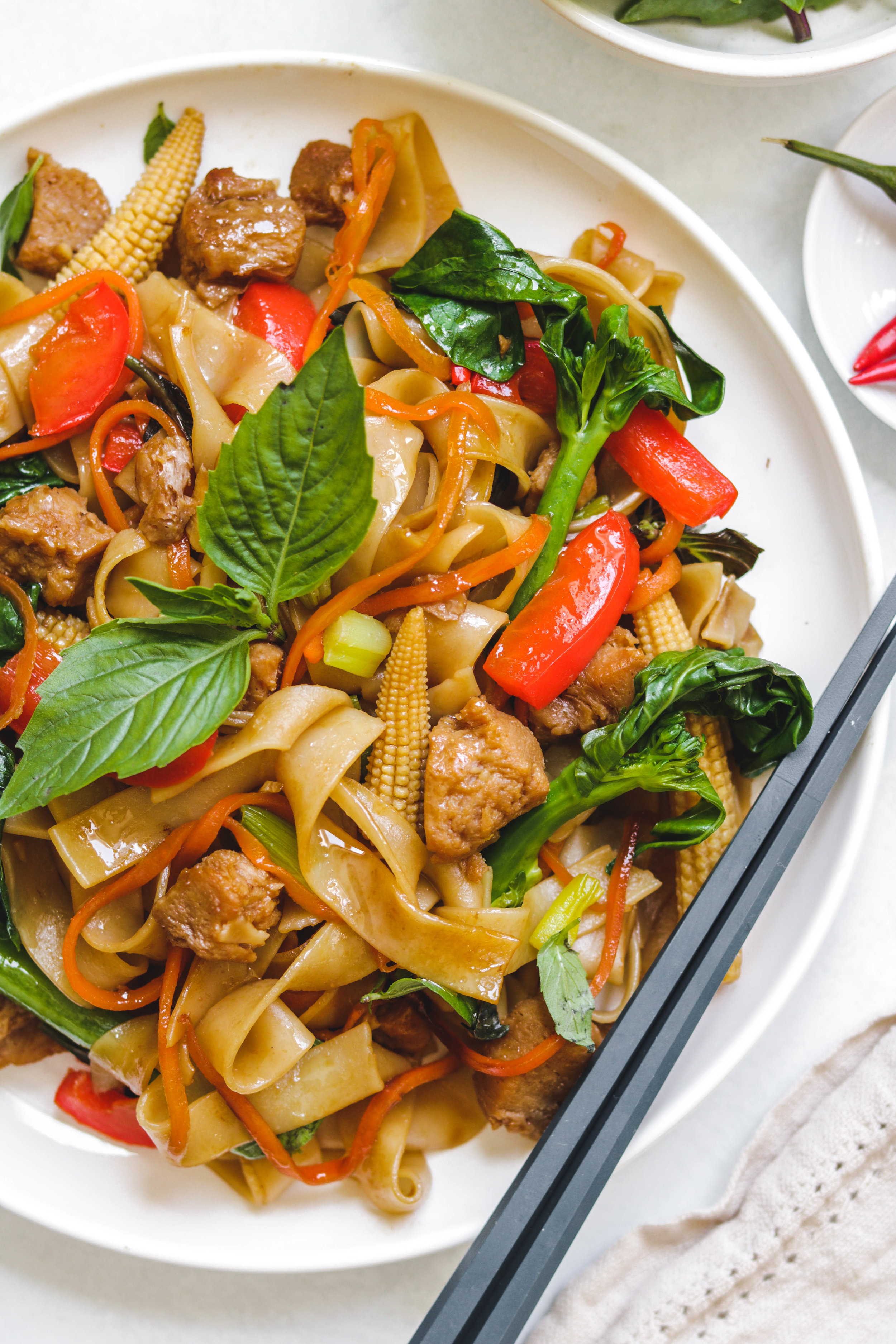 vegan thai drunken noodles on white plate close up