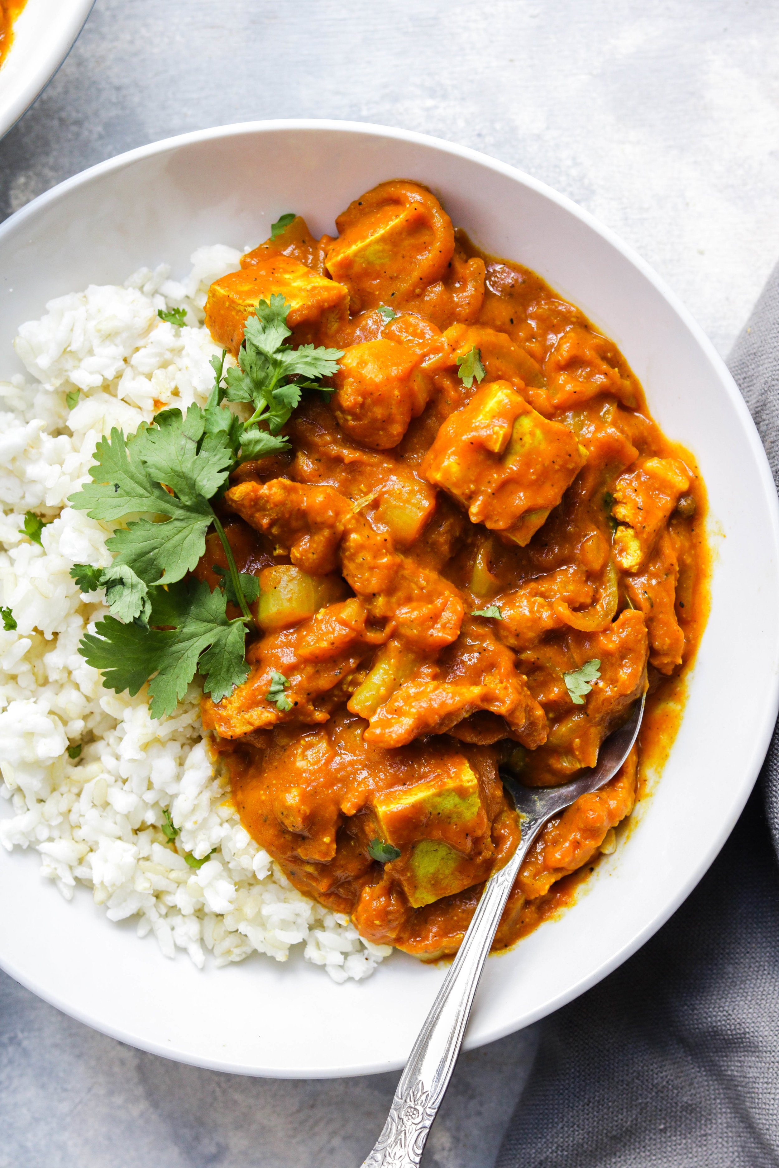 vegan butter chicken with white rice in a white bowl with cilantro closeup shot