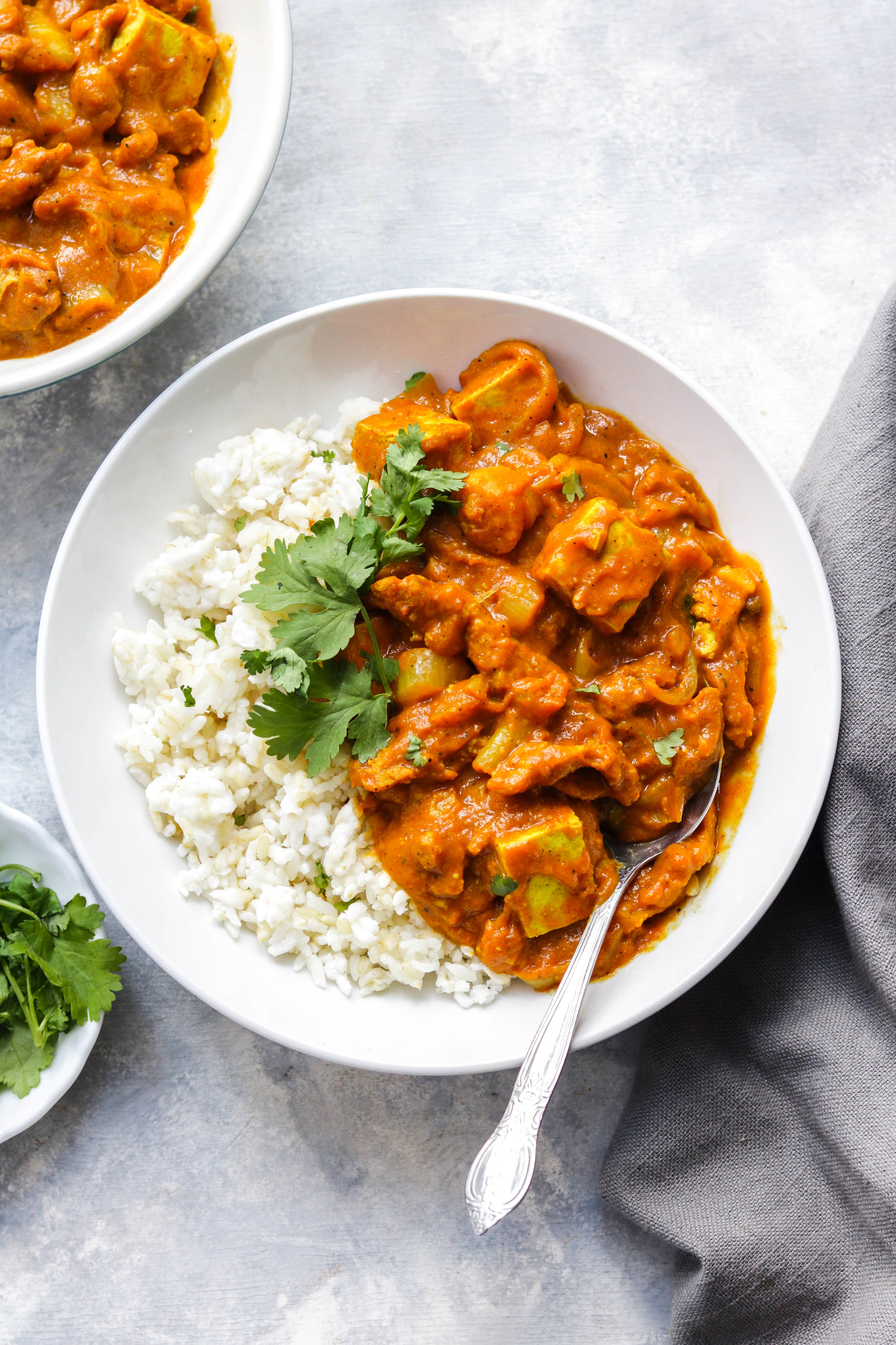 vegan butter chicken with white rice in a white bowl with cilantro
