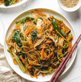 vegan japchae korean glass noodles on a white plate
