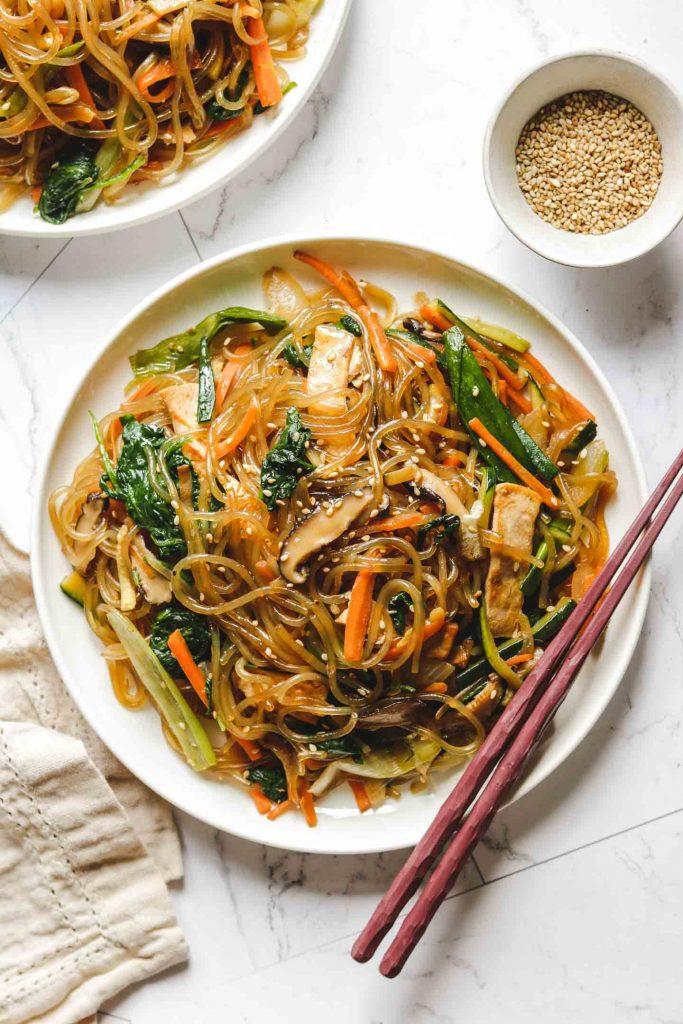 vegan japchae noodles on a white plate
