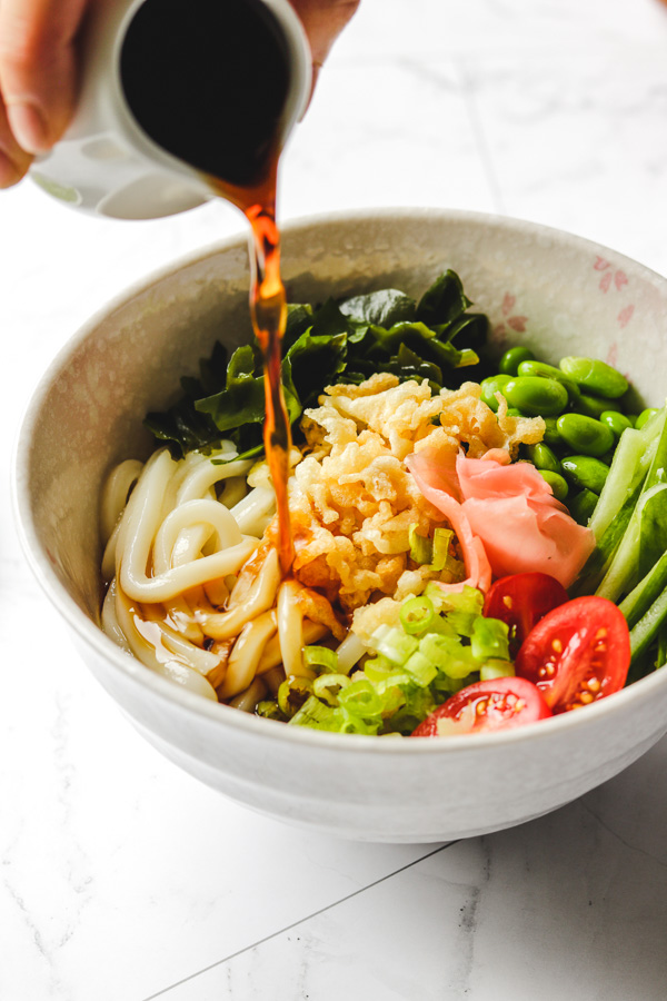 pouring udon dipping sauce in noodles