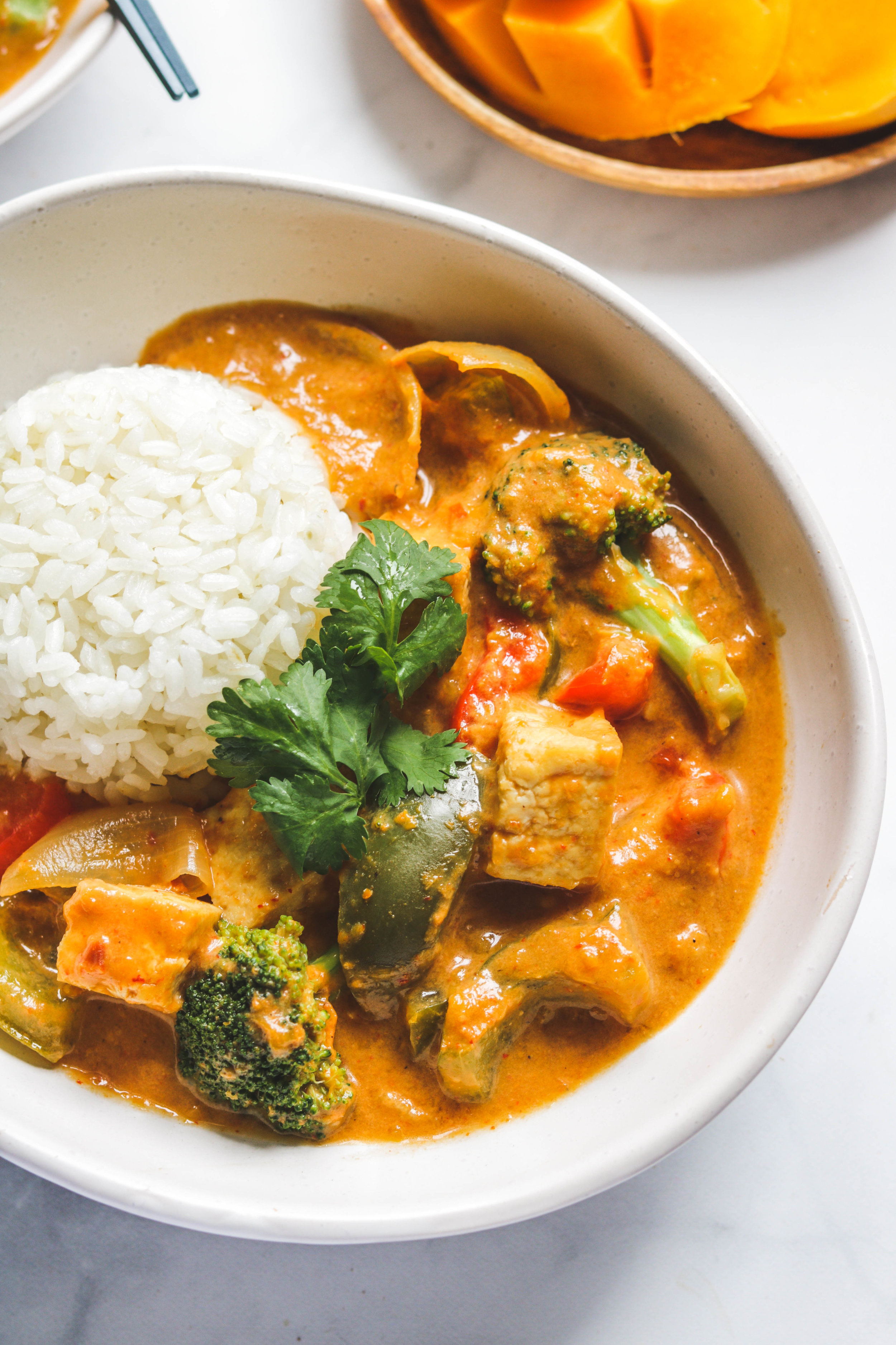easy thai mango coconut curry close up in white bowl