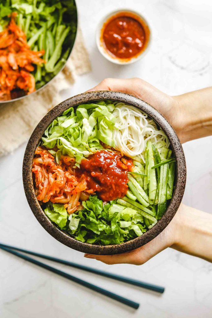holding korean spicy cold noodles in a brown bowl