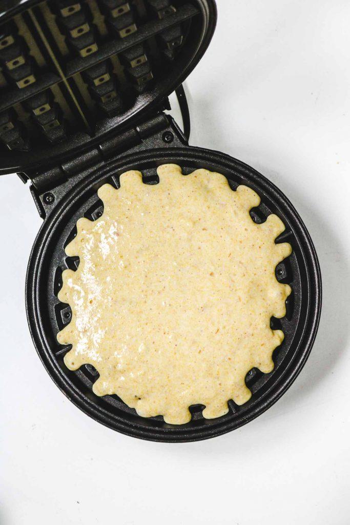 cornbread waffle batter on a waffle iron