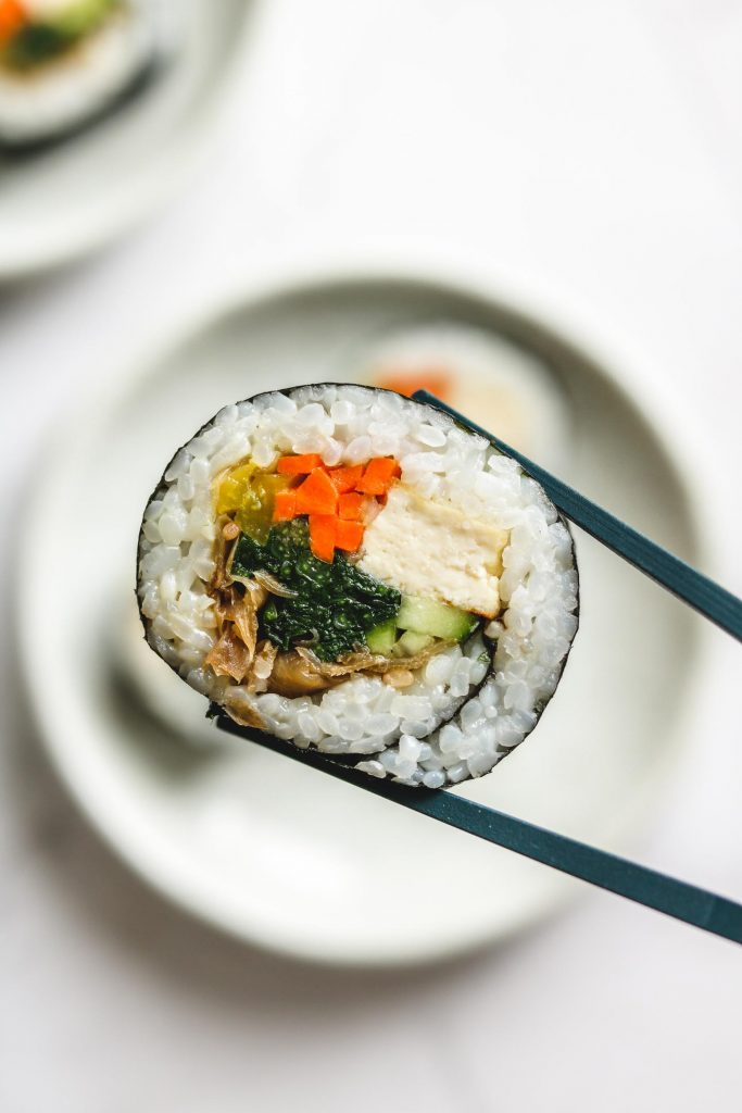 vegan kimbap holding with chopstick