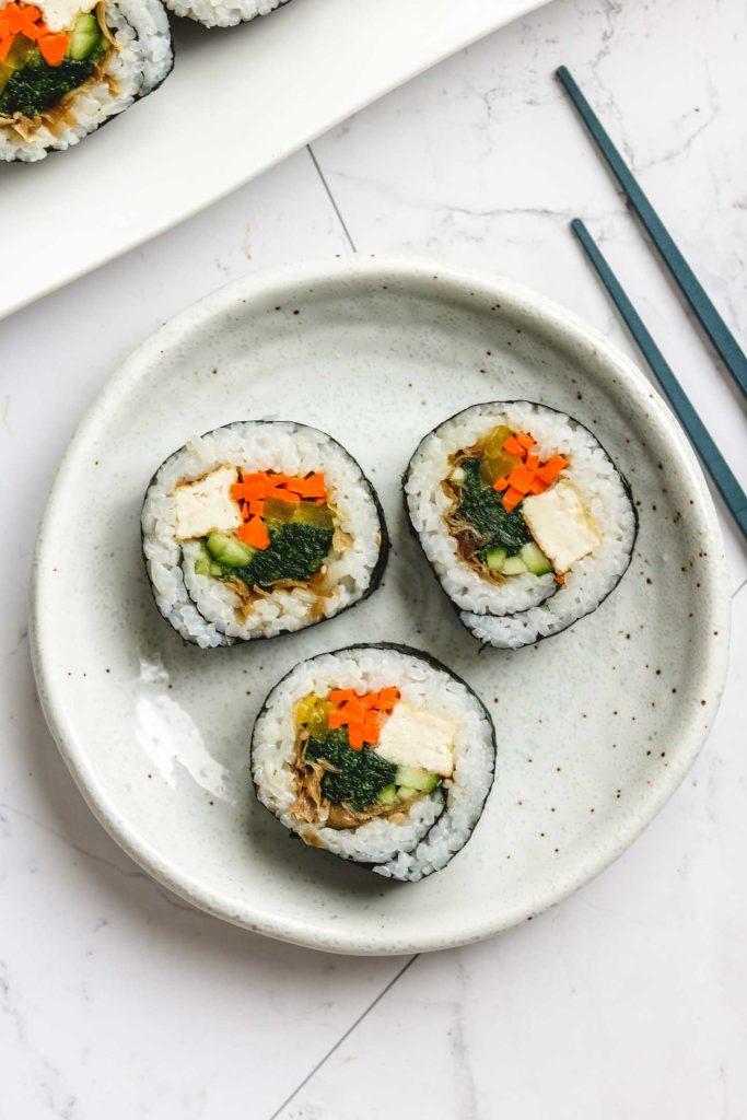 vegan kimbap with tofu on white plate