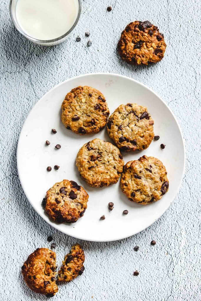 Air Fryer Tahini Chocolate Chunk Oatmeal Cookies on a white plate with a glass of milk