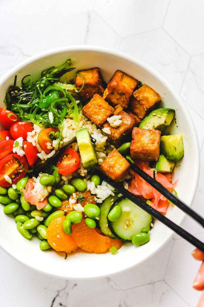 eating a tofu poke bowl with chopsticks