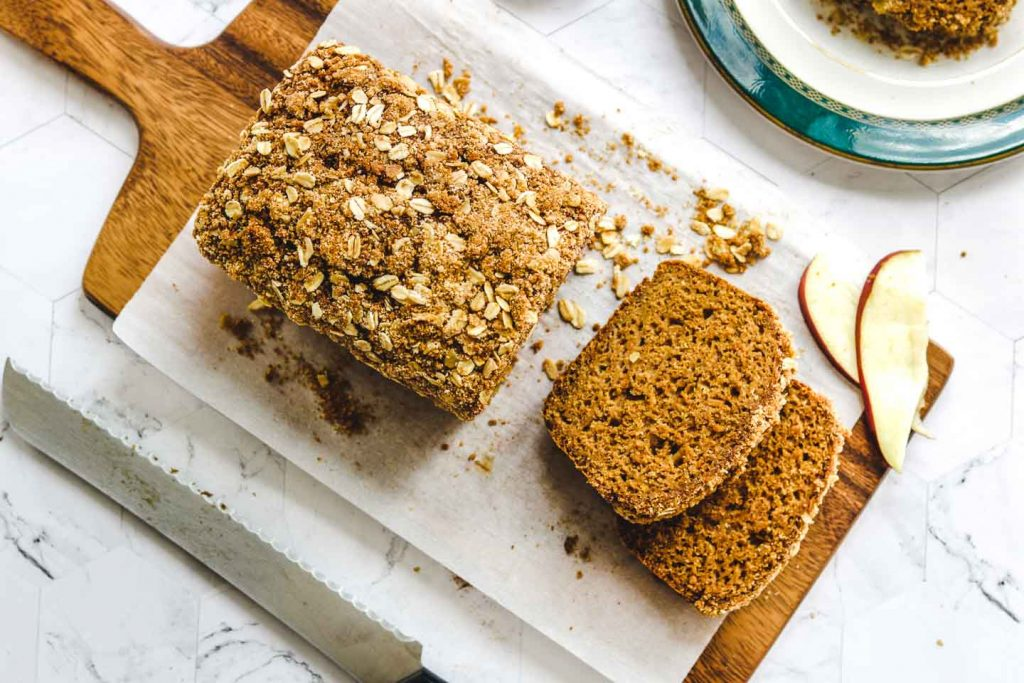 vegan apple bread with crumb topping landscape shot on wood board