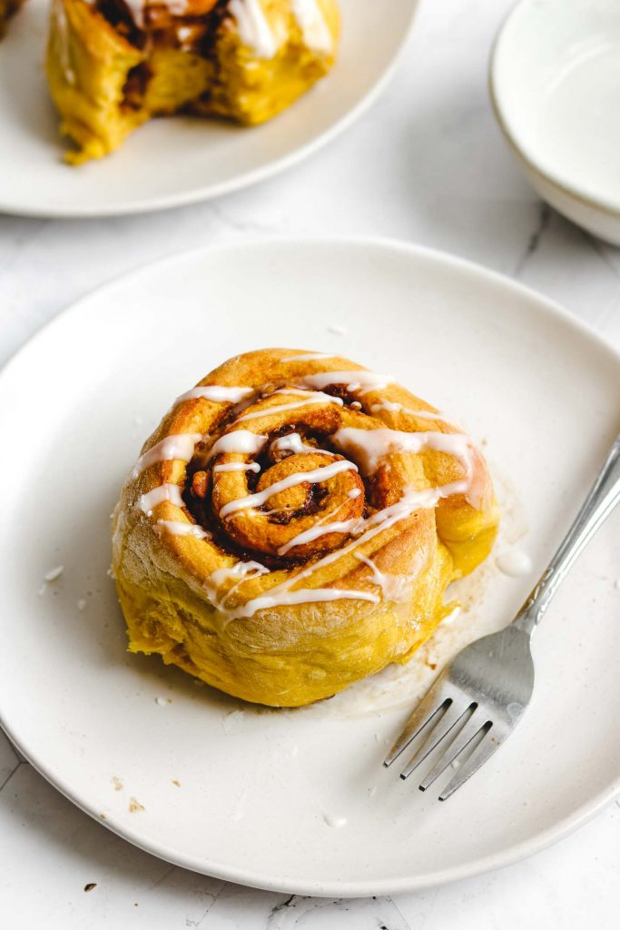 vegan gluten free pumpkin cinnamon roll with glaze on top on a white plate and fork angle shot