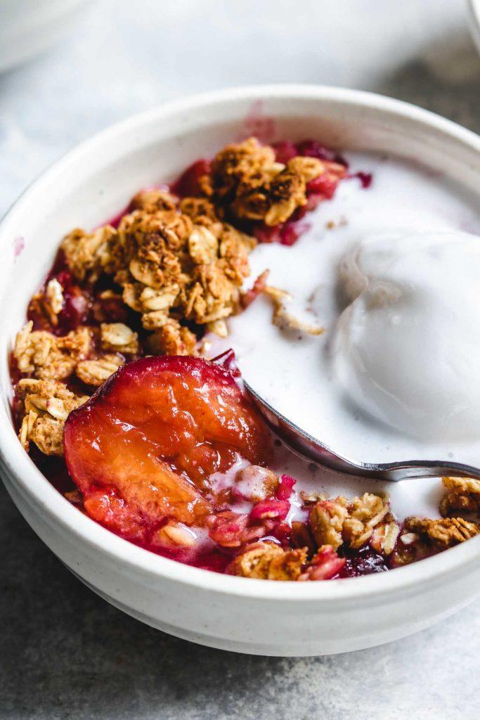vegan plum crisp in a bowl with non dairy ice-cream close up shot