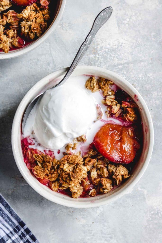 vegan plum crisp in a bowl with non dairy ice-cream