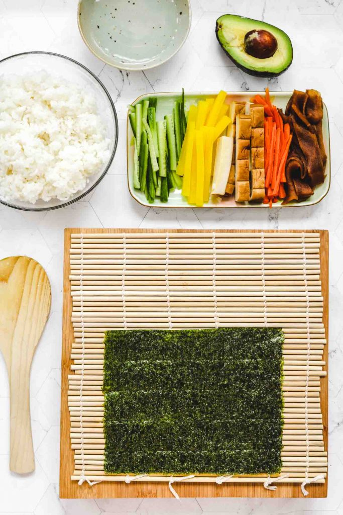 nori sheet on bamboo board with rice and vegetables