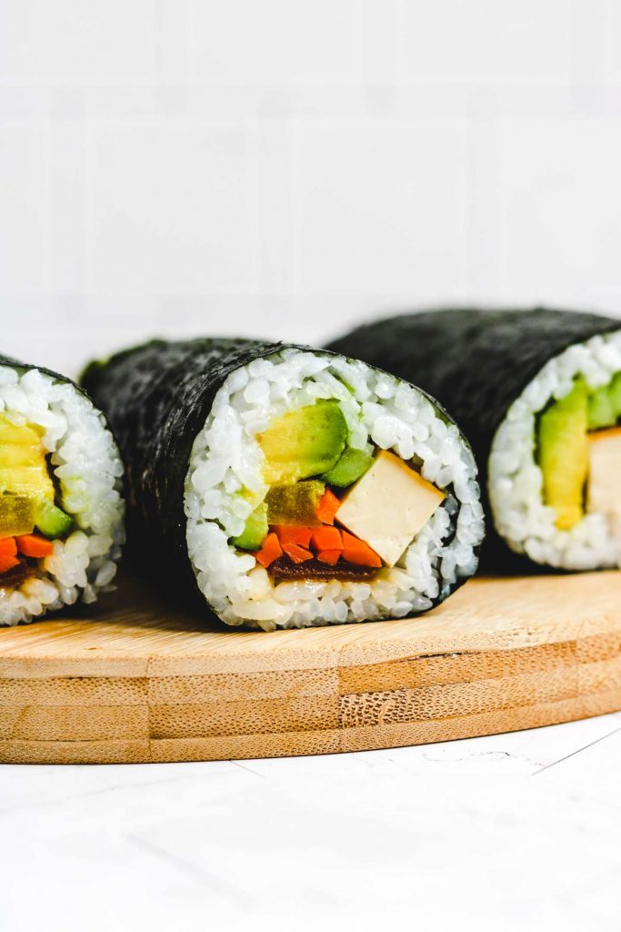 vegan take away sushi rolls on round bamboo board