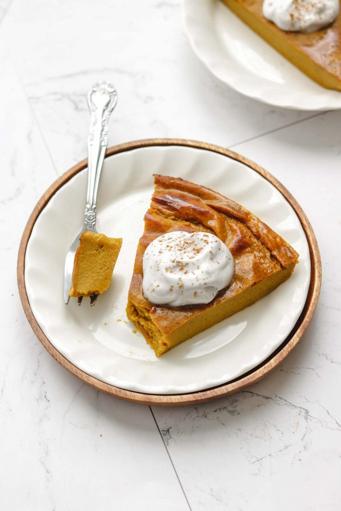 gluten free crustless pumpkin pie on a white plate with whip cream with fork