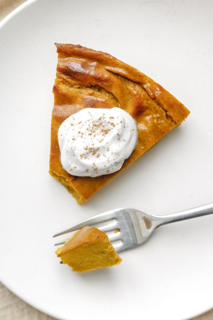healthy crustless pumpkin pie on a white plate with whip cream on a fork