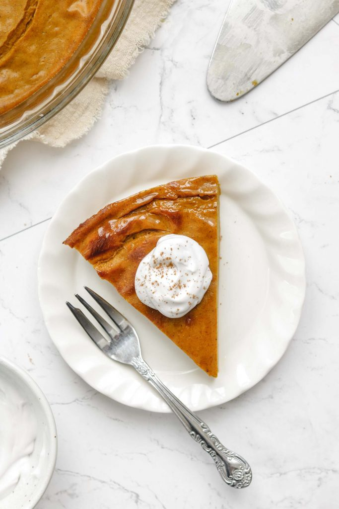 vegan crustless pumpkin pie on a white plate with whip cream