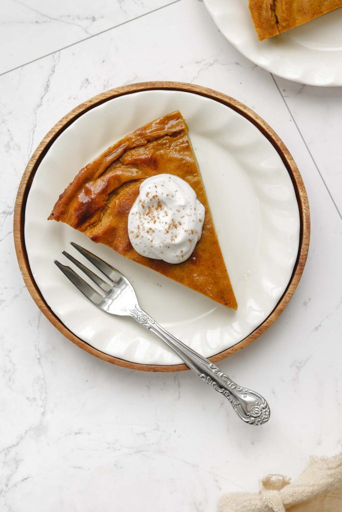 vegan crustless pumpkin pie on a white plate with whip cream and cinnamon