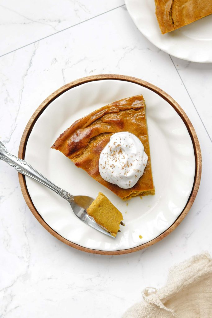 tofu crustless pumpkin pie on a white plate with whip cream