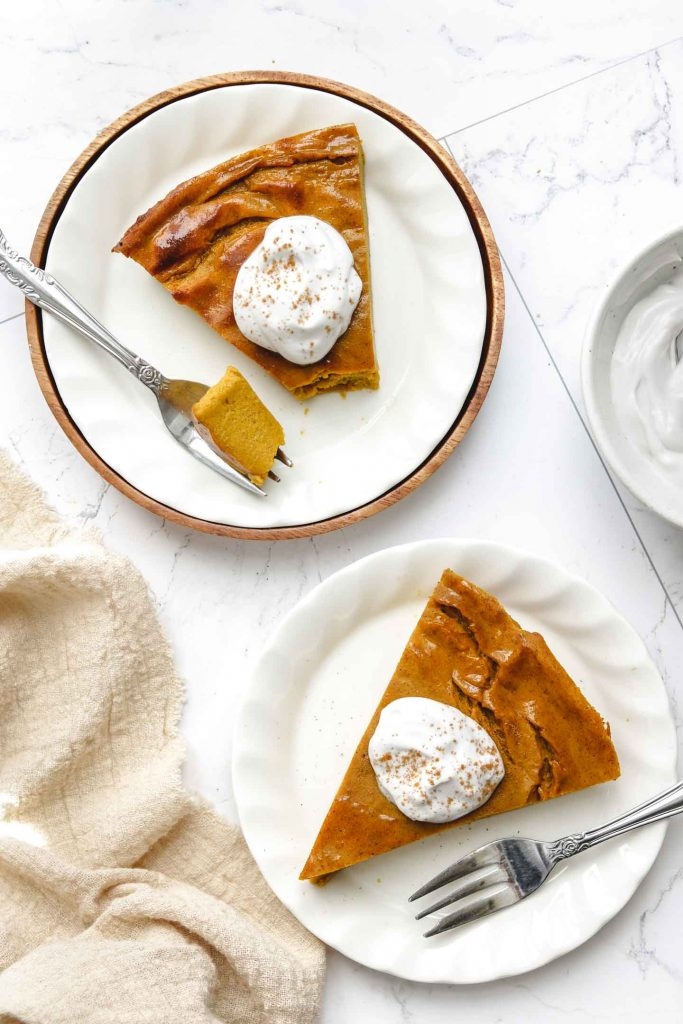 vegan impossible pumpkin pie on a white plate with whip cream with brown napkin