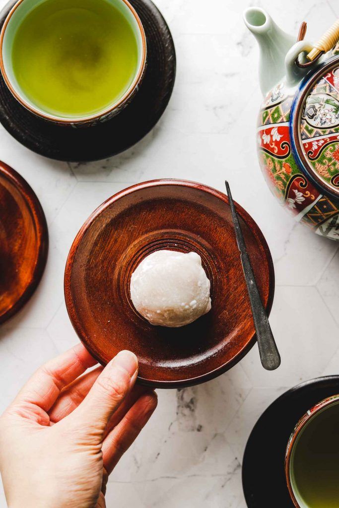 japanese pumpkin daifuku mochi on brown plate with hand in shot