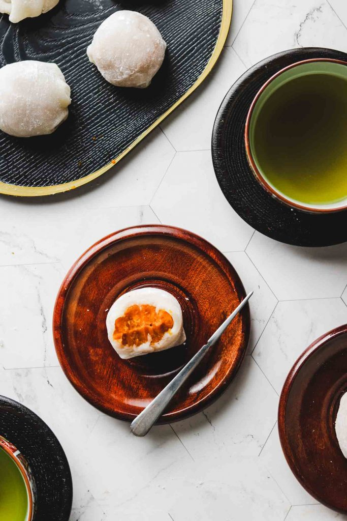 japanese kabocha pumpkin daifuku mochi on brown plate and green tea