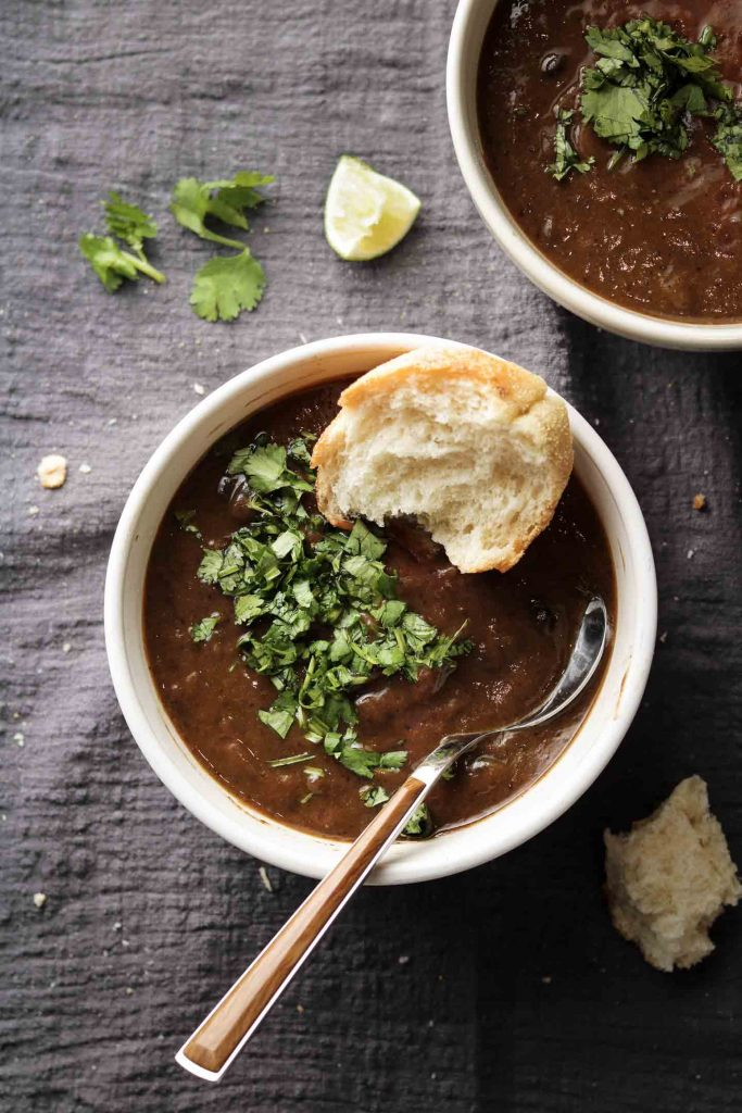 black bean soup in a white bowl with cilantro and bread