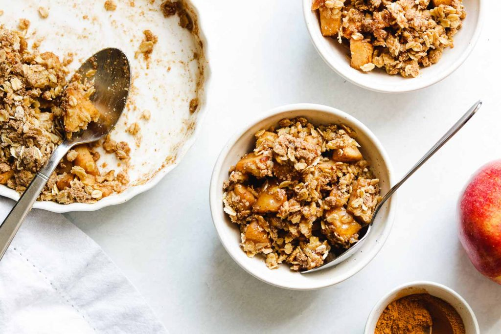 vegan gluten free apple crisp in a white bowl with ice cream and tart dish landscape photo