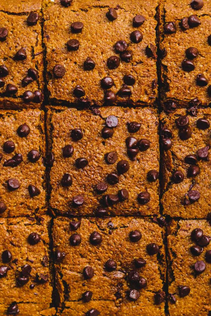 pumpkin spice vegan blondies with chocolate chips on top cut into 9 pieces