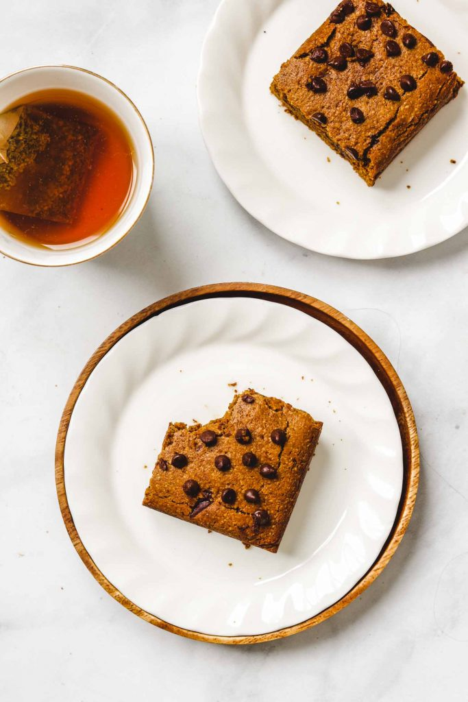 gluten free pumpkin blondies on a white plate with chocolate chips
