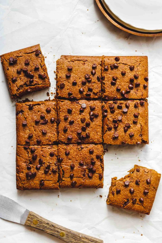 pumpkin spice vegan blondies with chocolate chips on top cut into 9 pieces on parchment paper