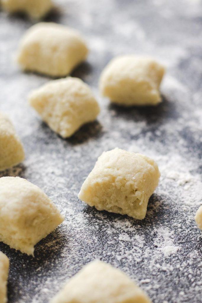 cauliflower gnocchi on a black surface with flour
