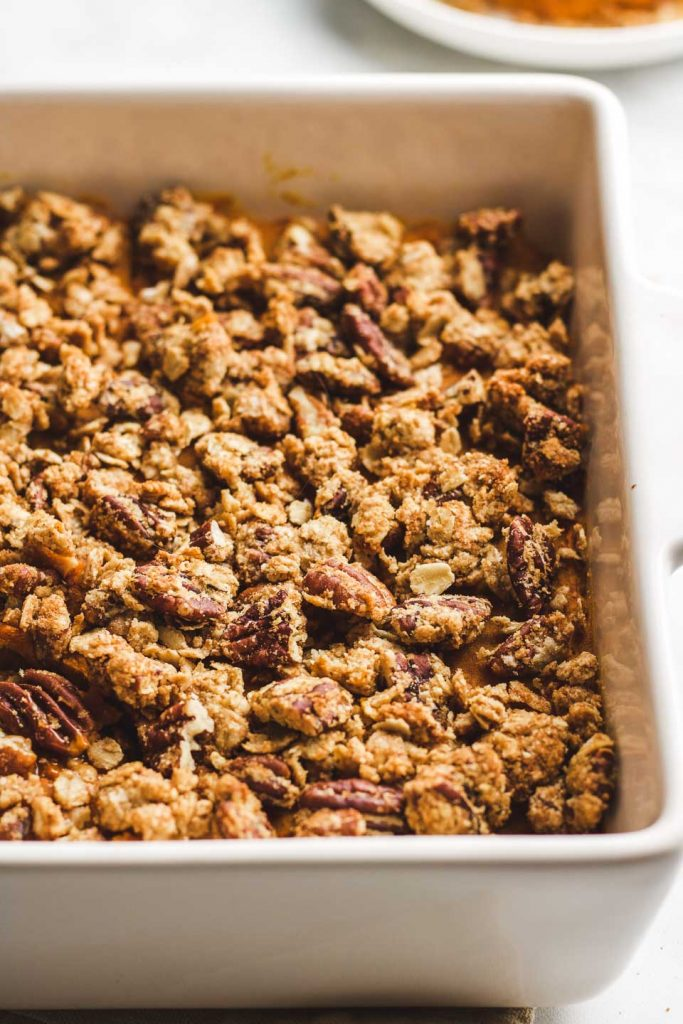 close up side shot of casserole with oat pecan crumble topping in a baking dish
