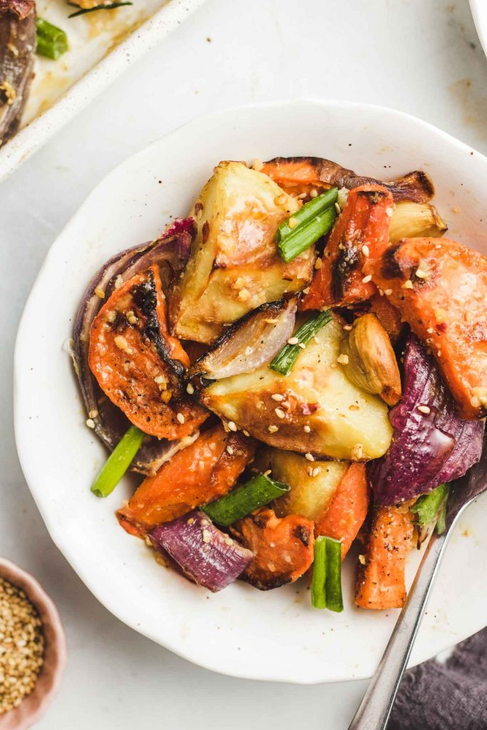 asian roasted root vegetable in a bowl with sesame seeds and green onions