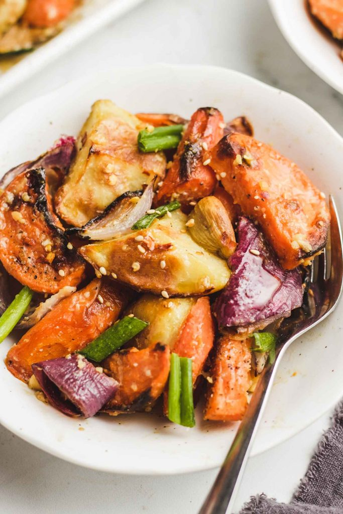 maple roasted root vegetable in a bowl with sesame seeds and green onions