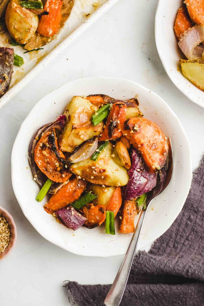 Miso Glazed Roasted Root Vegetables in a bowl with sesame seeds and green onions