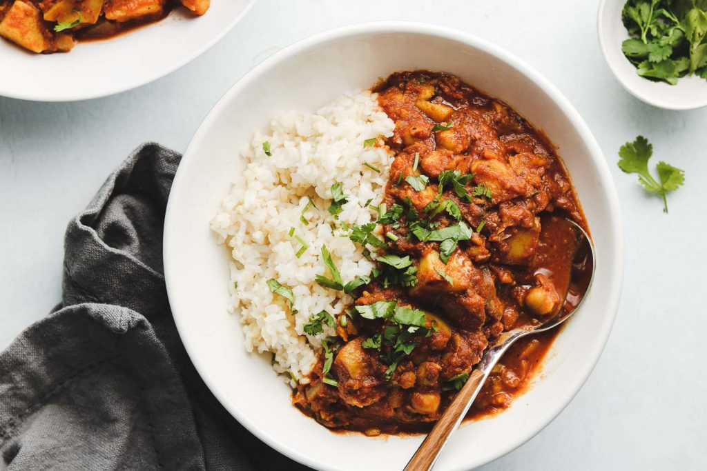 indian vegan bombay potatoes in a bowl with rice and cilantro on top landscape photo