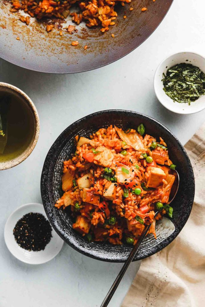 spicy korean rice in a black bowl with sesame seeds tofu and vegetables top shot