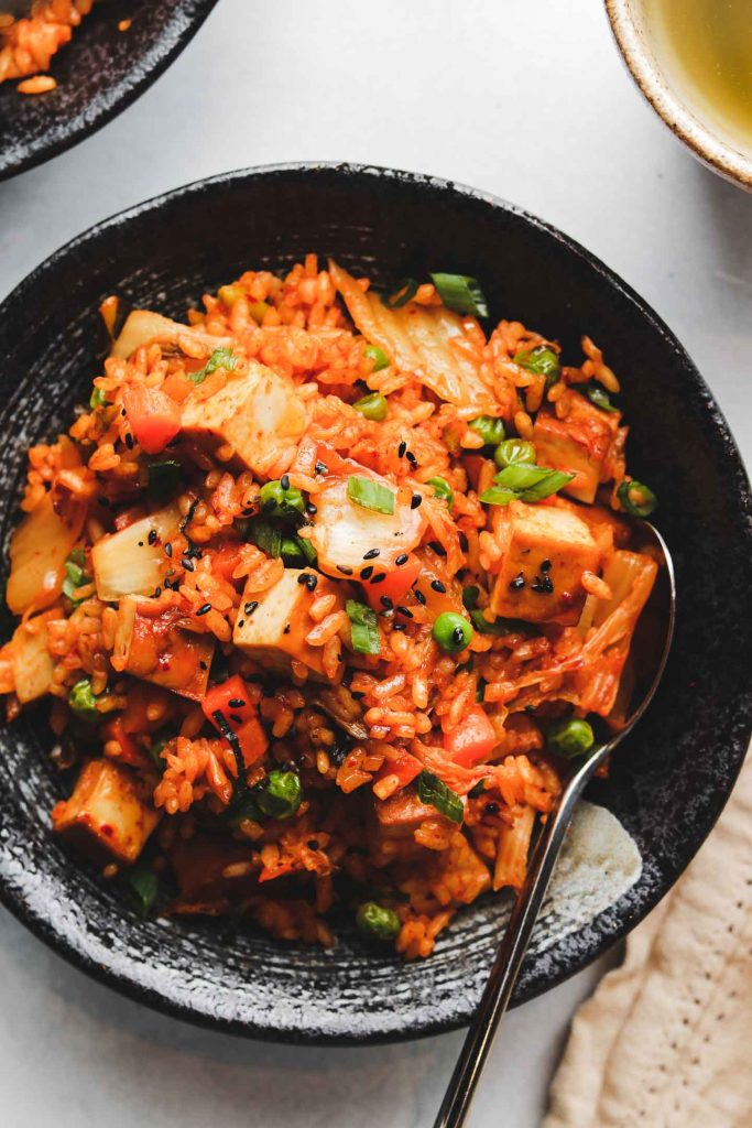 spicy korean rice in a black bowl with sesame seeds tofu and vegetables