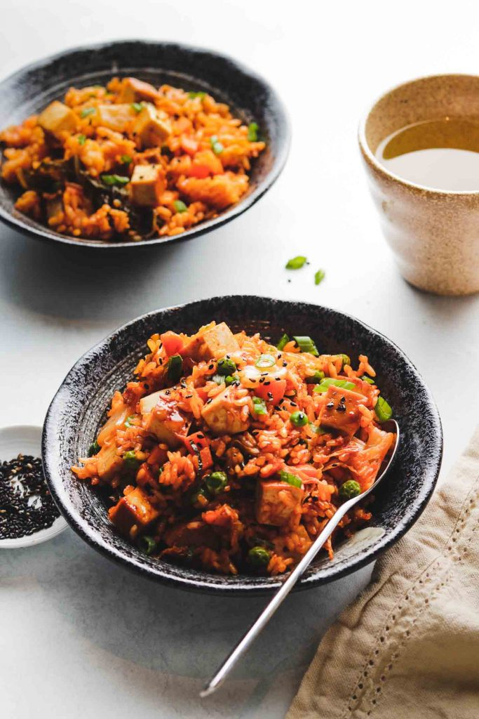 vegan kimchi fried rice in a black bowl landscape photo 3/4 shot with green tea