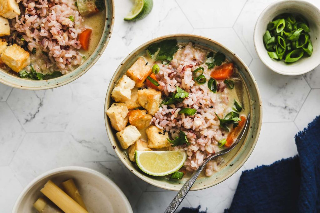 lemongrass ginger thai coconut soup with purple rice and puff tofu in a bowl with a spoon landscape photo