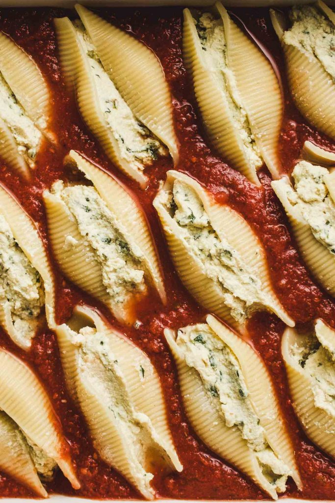 vegan pesto ricotta stuffed shells in a baking tray un baked