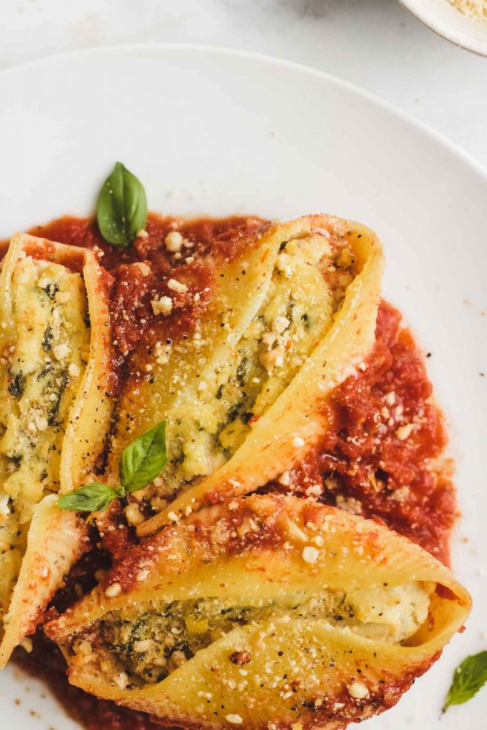 vegan stuffed shells with tofu ricotta and marinara closeup shot